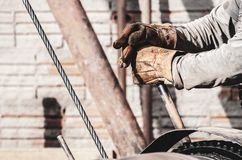 Worker hands pulling the lever of a pile driver. Bate-estaca. Construction worker. Two hands holding a lever. Worker hands wearing worn out gloves triggering a royalty free stock images