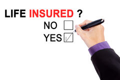 Worker hands with a question of life insured. Hands of male manager using a pen while choosing a yes option on the whiteboard with a question of life insured Royalty Free Stock Photography
