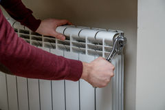 Worker hands repairing radiator with wrench. Close-up Royalty Free Stock Images