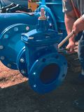Worker hands screwing Gate valve with nuts on piping. Royalty Free Stock Photos