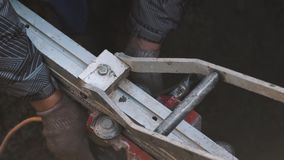 Worker hands turning wrench on piece of metal industrial machinery in ditch stock video