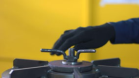 Worker Hands twist metal part. Slow Motion. Worker with gloves spins metal part stock footage