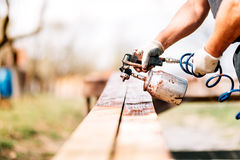 worker hands using airbrush and spray gun for painting timber stock image