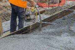 Worker hands using concrete vibrator Stock Photos
