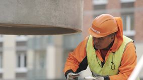 Worker in hard hat brushing bottom of concrete manhole ring, hanging on chains stock video footage