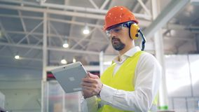 A worker in hard hat and headset types information on his gadget, looking at goods at a warehouse. stock video footage
