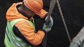 Worker in hard hat hold chains to stand on concrete manhole ring in dirty trench stock video