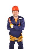 Worker in hard hat holding hammer and pliers. Royalty Free Stock Image