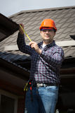 Worker in hard hat measuring size of house roof Royalty Free Stock Photography