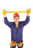 Worker in hard hat raising ruler Stock Image
