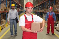 Worker in hardhat with parcel at the front of team. Of workforce in warehouse.2or3 people in background royalty free stock image