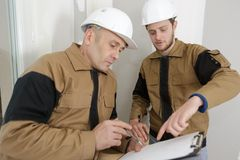 Worker with hardhat taking notes on clipboard. Worker with hardhat taking notes on his clipboard Royalty Free Stock Image