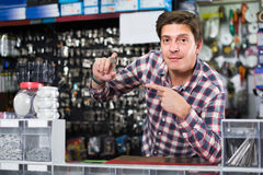 Worker in hardware store trading goods and keys in uniform. Cheerful spanish worker in hardware store trading goods and keys in uniform Royalty Free Stock Photography