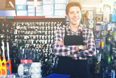 Worker in hardware store trading goods for water tap in uniform. Cheerful worker in hardware store trading goods for water tap in uniform Royalty Free Stock Images