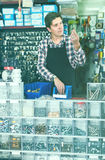 Worker in hardware store trading goods for water tap in uniform. Cheerful russian worker in hardware store trading goods for water tap in uniform Royalty Free Stock Photo