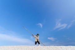 Worker is harvesting sea salt at salt field. Minimal Composition Stock Photos