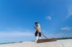 Worker is harvesting sea salt at salt field. Royalty Free Stock Photos
