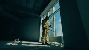 Worker in a hazmat suit is sanitizing a large window