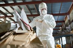 Worker in Hazmat Suit Sorting Cardboard at Recycling Plant. Low angle portrait of factory worker wearing biohazard suit sorting reusable cardboard on waste stock photos