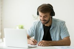 Worker in headphones listening to audio course writing important. Smiling man in headphones watching webinar, listening to web audio course, making notes and stock image