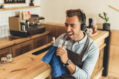 Worker cleaning glassware. Worker in headphones pretending singing while cleaning glassware in coffee shop stock photography