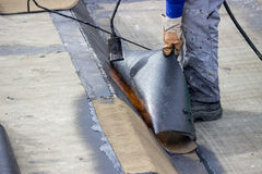 Worker heating and melting bitumen felt 2 Stock Photo