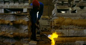 Worker heating metal mold with blow torch in foundry workshop 4k. Worker heating metal mold with blow torch in foundry workshop. Worker working in foundry stock footage