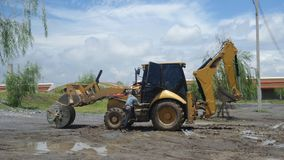 Worker and Heavy equipment backhoe  in construction site under blue sky Stock Image