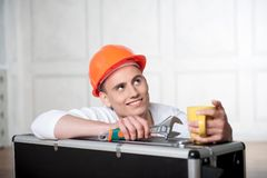 Worker in helmet with coffee cup Royalty Free Stock Images