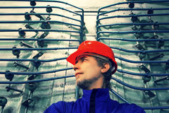 The worker in a helmet at factory.Industrial interior. Stock Photo