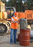 Worker in helmet holding a canister of fuel. Male worker in helmet holding a canister of fuel for Construction machinery Royalty Free Stock Photos