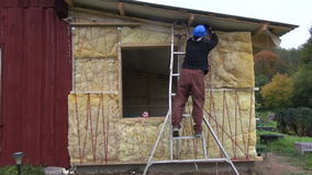 Worker with helmet insulating with rock wool wooden house wall stock video footage