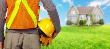 Worker with helmet in orange security vest. Royalty Free Stock Image