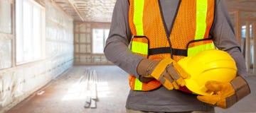 Worker with helmet in orange security vest. Stock Photos