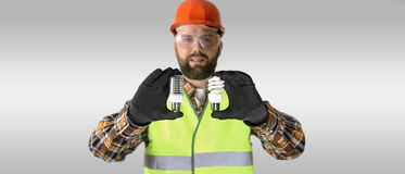 Worker in a helmet and protective clothing with a light bulb in Stock Image