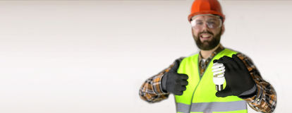Worker in a helmet and protective clothing with a light bulb in Royalty Free Stock Images