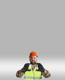Worker in a helmet and protective clothing with a light bulb in Royalty Free Stock Photography