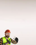 Worker in a helmet and protective clothing with a light bulb in Royalty Free Stock Photos