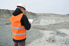 Worker in a helmet. And quarry in background Royalty Free Stock Image