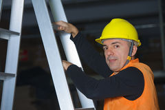 Worker in helmet rests on the ladder Stock Photo