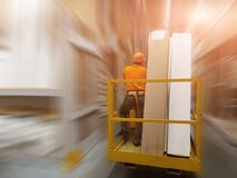 Worker in helmet with safety belt on forklift with goods in big building supermarket. Storage at warehouse. Accident prevention an Royalty Free Stock Image