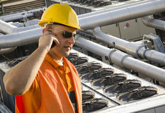 Worker with helmet and sunglasses talking on mobile phone Royalty Free Stock Images