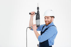 Worker in helmet using drill and pointing up Royalty Free Stock Image