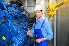 Worker with helmet working on big generator showing thumb up royalty free stock image