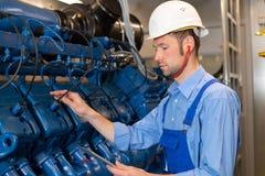 Worker with helmet working on big generator stock photo