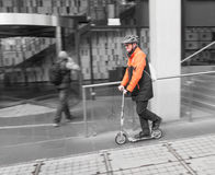 Worker in Hi-Vis Commutes on Scooter. A worker in a Hi-Vis jacket and helmet in Melbourne, Australia commutes to work on his scooter Royalty Free Stock Photography