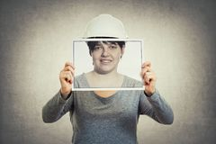 Worker hiding private life. Young woman engineer wearing protective helmet, holding a paper photo covering her face, like a mask for hiding the true emotion royalty free stock photo