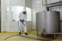 Worker with high pressure washer cleaning floor. Worker in white protective uniform,mask,,gloves  with high pressure washer at  large industrial process tank Royalty Free Stock Photography