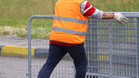 Worker with high visibility reflective jacket moves iron hurdles Royalty Free Stock Image