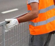 Worker with high visibility reflective jacket moves iron hurdles Royalty Free Stock Photo